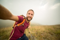 Healthy young man hiking taking selfie